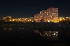 A vista da terraplenagem da universidade abriga 28, 30, 32 e 34 Reflexão de luzes da noite das casas no rio Miass imagens de stock