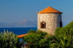Vista da torre do moinho de vento do grego clássico, do mar e da planta de energias eólicas distante na parte superior da montanh fotografia de stock