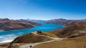 Vista da un passo di montagna ad un lago ad alta altitudine del blu luminoso, di una strada, di piccolo padiglione e di una caten Fotografia Stock Libera da Diritti