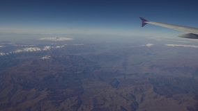 Vista da una finestra dell'aeroplano sulle montagne fotografia stock libera da diritti