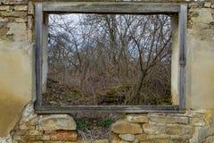 Vista da una finestra di legno di vecchia casa di rovina vicino alla foresta Fotografie Stock