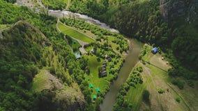 Vista da una grande altezza ad un villaggio calmo al piede delle montagne e del fiume Paesaggio molto bello della montagna archivi video