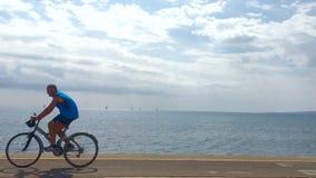 Vista da una tavola del caffè verso l'oceano e dai ciclisti interrotti parcheggiando automobile archivi video