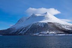 Vista da viagem do barco no fiorde nevado bonito com uma nuvem sobre no mar norueguês no céu azul, Noruega Fotos de Stock Royalty Free