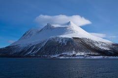 Vista da viagem do barco no fiorde nevado bonito com uma nuvem sobre no mar norueguês no céu azul, Noruega Imagem de Stock Royalty Free