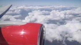 Vista da vigia às nuvens Vista da janela do plano na asa de um avião com um motor de jato vídeos de arquivo