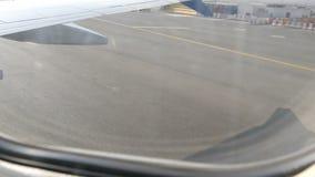 Vista da vigia do plano à pista de decolagem O plano está preparando-se para a decolagem filme