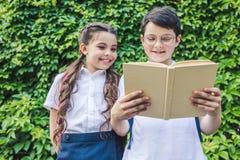 vista dal basso del libro di lettura felice degli scolari insieme davanti a fotografia stock libera da diritti