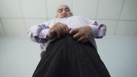 Vista dal basso del maschio corpulento che zippa i suoi pantaloni con grande sforzo, sovrappeso video d archivio