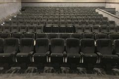 Vista dal basso del modo al corridoio del cinema con le sedie molli nere fotografie stock
