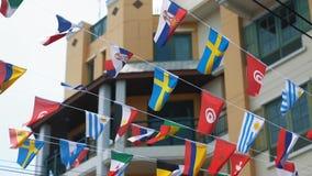 Vista dal basso delle bandiere dei cittadini che ondeggiano sopra la testa nel cielo blu Movimento lento, bandiere di parecchi pa stock footage
