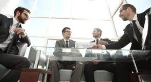Vista dal basso Gente di affari che si siede al tavolo delle trattative fotografie stock libere da diritti