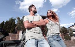 Vista dal basso marito e moglie che fanno una pausa la loro automobile fotografia stock