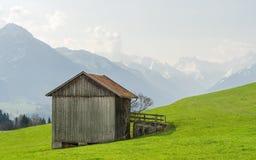 Vista dal granaio di legno alle montagne innevate nella primavera Immagini Stock