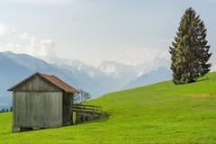 Vista dal granaio di legno alle montagne innevate nella primavera Fotografia Stock Libera da Diritti