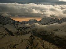Vista dal punto di vista di elevata altitudine nelle alpi sulle montagne innevate nella sera di inverno Immagini Stock Libere da Diritti