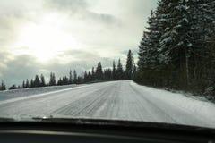 Vista dal sedile del ` s del driver sulla strada coperta di neve, forte blindi fotografia stock