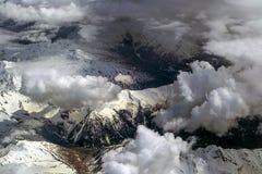 Vista dall'aereo alle alpi nevose sotto le nuvole Fotografie Stock