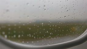 Vista dall'aereo sul grembiule attraverso la finestra con le gocce di pioggia video d archivio