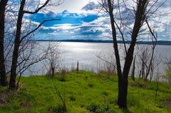 Vista dall'alta banca del fiume allo splendore di acqua nei raggi del sole in aumento della molla Fotografia Stock Libera da Diritti