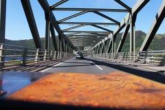 Vista dall'automobile sulla strada e sul ponte d'acciaio in altopiani scozzesi Immagini Stock Libere da Diritti