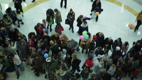 Vista dall'elevatore di vetro alla folla della gente all'evento festivo nel centro commerciale stock footage