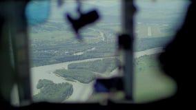 Vista dall'interno della cabina di pilotaggio dell'elicottero dei prati e dei campi stock footage