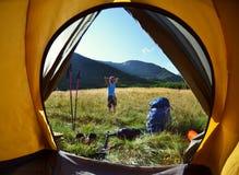 Vista dall'interno di una tenda sulla ragazza e sulle montagne Fotografia Stock Libera da Diritti