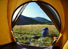 Vista dall'interno di una tenda sulla ragazza e sulle montagne Fotografia Stock