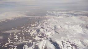 Vista dall'oblò dell'aeroplano sulle montagne innevate del Caucaso archivi video