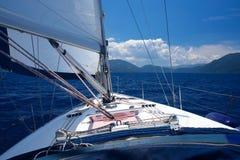 Vista dalla cabina di pilotaggio di una barca a vela che guarda in avanti La vela principale è aperta immagini stock