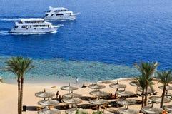 Vista dalla cima ad una bella spiaggia sabbiosa con le chaise-lounge del sole, i letti del sole e gli ombrelloni sulla vacanza in fotografia stock