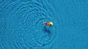 Vista dalla cima come donna in un costume da bagno rosso e nuotate gialle nelle grandi di un cappello nello stagno video d archivio