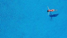 Vista dalla cima come una donna in un costume da bagno rosso nuota il dorso nello stagno stock footage