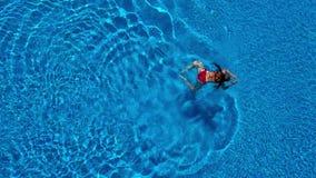 Vista dalla cima come una donna in un costume da bagno rosso nuota nello stagno stock footage