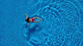 Vista dalla cima come una donna in un costume da bagno rosso nuota nello stagno archivi video