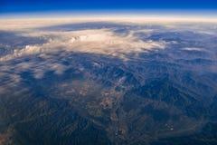 Vista dalla finestra degli aerei sulle nuvole e sulle montagne Immagini Stock