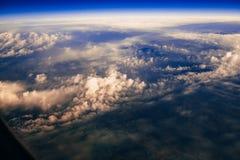 Vista dalla finestra degli aerei sulle nuvole e sulla terra da un'altezza Fotografia Stock