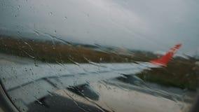 Vista dalla finestra dell'aereo sulle gocce di pioggia sul vetro, movimento lento video d archivio