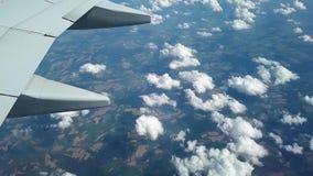 Vista dalla finestra dell'aereo sulle nuvole e sulla terra, volante sopra le nuvole stock footage