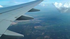 Vista dalla finestra dell'aeroplano sull'ala, sulle nuvole e sulla terra, volante sopra le nuvole video d archivio
