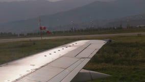 Vista dalla finestra sull'ala di un aeroplano che si muove lungo la pista all'aeroporto dopo l'atterraggio stock footage