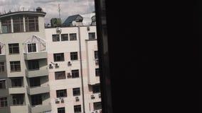 Vista dalla finestra sulla facciata di grande nuova alta costruzione grigia e del cielo nuvoloso sopra  stock footage