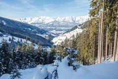 Vista dalla montagna con una foresta nella valle con neve o Fotografia Stock