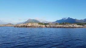 Vista dalla navigazione dell'yacht lungo la costa delle isole di Lofoten con le piramidi per l'essiccazione del merluzzo archivi video