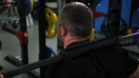 Vista dalla parte posteriore L'uomo si accovaccia con un bilanciere 4K Mo lento archivi video