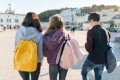 Vista dalla parte posteriore su tre studenti della High School Fondo della città, ora dorata immagini stock