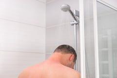 Vista dalla parte posteriore su un giovane che prende una doccia Fotografia Stock Libera da Diritti