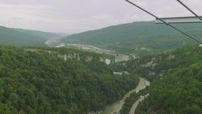 Vista dalla piattaforma di osservazione del ponte sospeso del metallo alla valle verde della montagna con la strada ed il fiume q archivi video