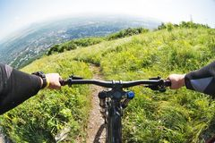 Vista dalla prima persona di un ciclista che guida in discesa da un'alta montagna nei precedenti di una città nella distanza Immagini Stock Libere da Diritti